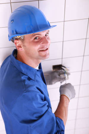 Smiling electrician wiring a wall socket photo