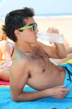 Teenager drinking water on the beach photo