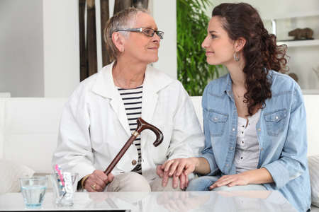 young woman helping senior lady at home photo