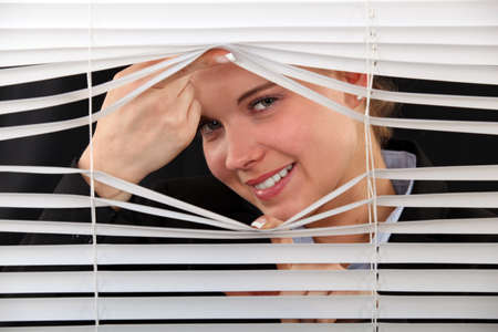 woman looking through the blinds photo