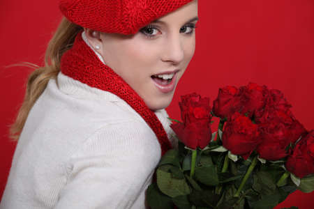 sweater girl: Young woman holding bunch of roses Stock Photo