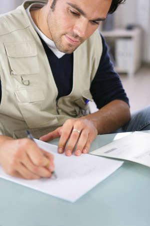 hombre escribiendo: Hombre escribiendo en un pedazo de papel Foto de archivo