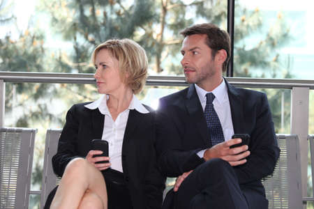 25 29 years: Business executives sitting on a bench texting Stock Photo