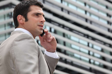 Young man talking on phone outdoors photo