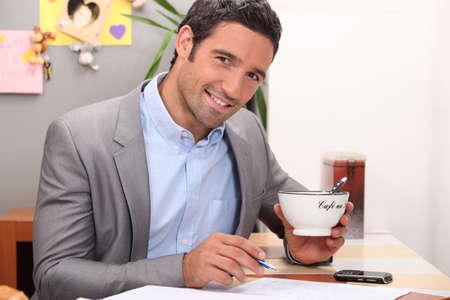 Businessman working in his kitchen with a cup of coffee photo