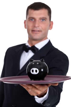 Waiter serving a piggy bank Stock Photo - 11912359