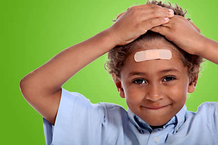 coloured little boy with plaster on his forehead against fluorescent green background photo