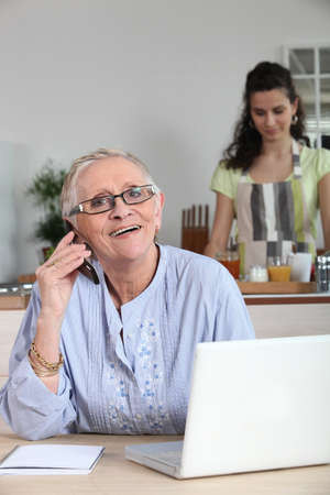 Elderly woman on the phone and surfing the internet photo