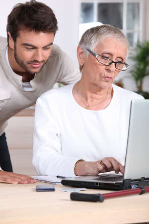 Man teaching woman to use laptop photo