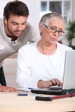 Man teaching woman to use laptop photo