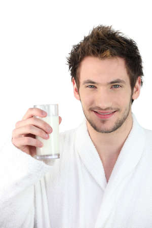 Man in dressing gown drinking glass of milk photo