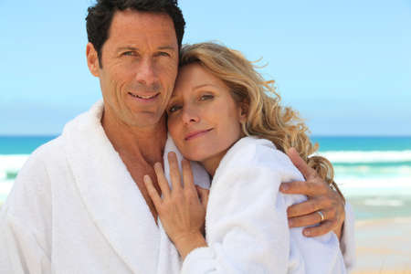 mid aged couple wearing a bathrobe near the sea photo