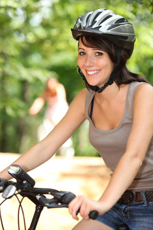 bicycle helmet: Woman riding her bicycle Stock Photo