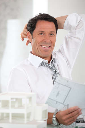 Smiling, relaxed architect looking at plans Stock Photo