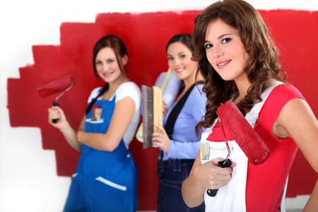 Three women painting a wall in red. photo