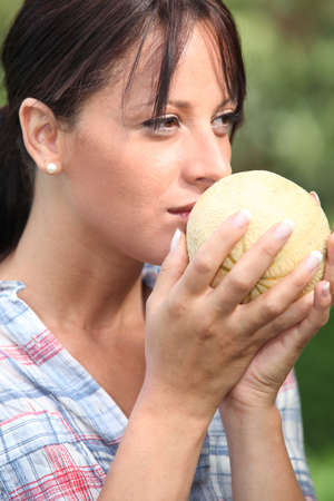 ripeness: Young woman smelling a melon