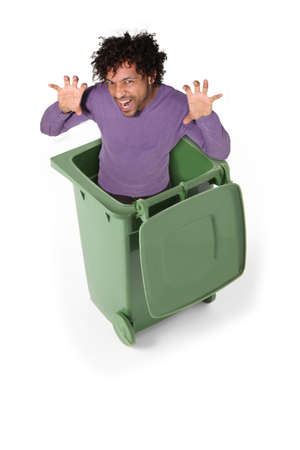coloured man in green dustbin imitating tiger photo