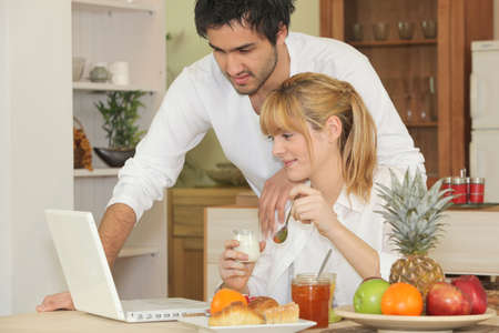 Couple with laptop having breakfast photo