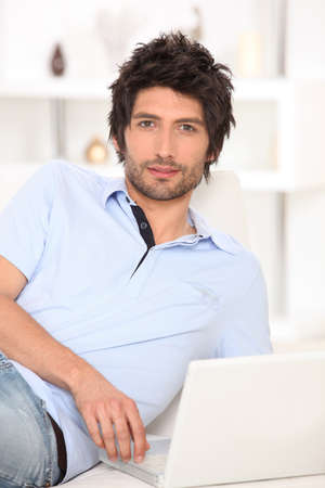 Man looking at his laptop in bed photo