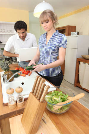 Young woman preparing salad in kitchen photo