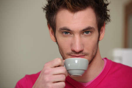 straight faced: A serious man drinking a cup of coffee