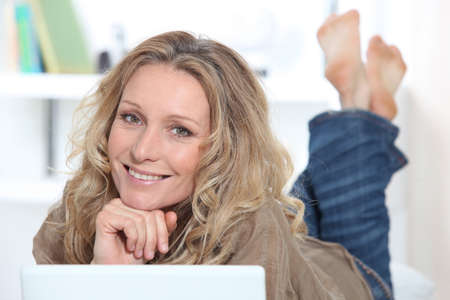 Smiling happy woman using a laptop photo