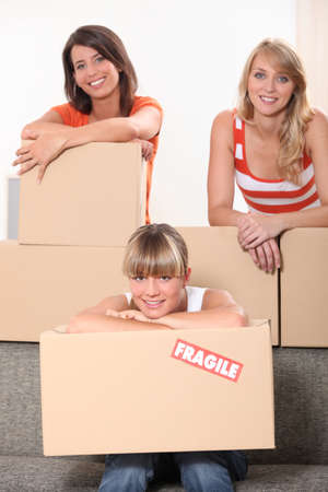 three young women posing in a room full of unpacked packages photo