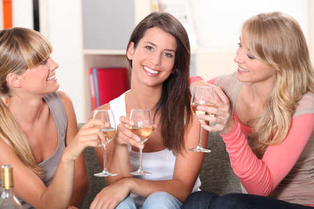 three girlfriends drinking wine together photo