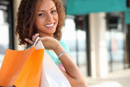 買い物袋を運ぶメティス女性の笑みを浮かべてください。