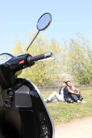 Couple relaxing in a park next to their scooter Stock Photo - 11913632