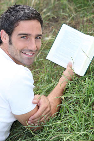 Man lying in the grass reading a book photo