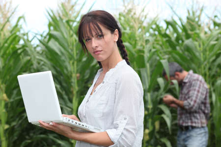 agricultural: Farming couple with a laptop in a field of corn Stock Photo
