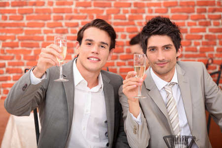Young men in suits drinking champagne photo
