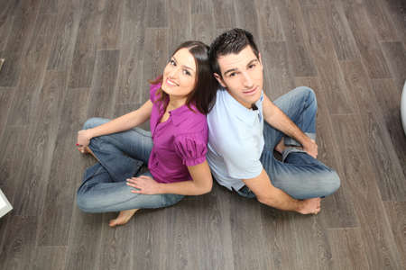 two floors: Couple sat back to back on laminate flooring