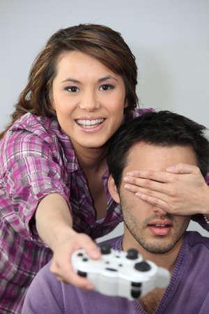 ojos vendados: Pareja joven divirtiéndose sobre una consola de juegos Foto de archivo