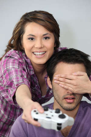 Young couple larking about with a games console photo