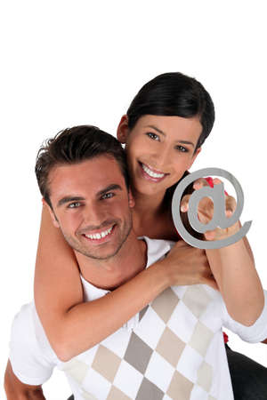 electronic mail: Couple holding an at symbol