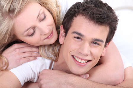 arms behind head: lovely young couple cuddling