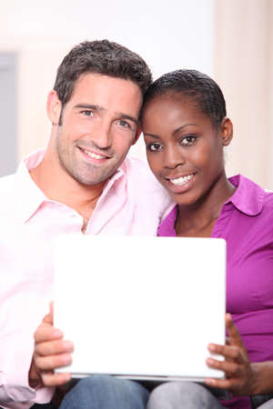 beauteous: mixed couple heads joined with laptop