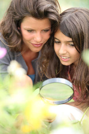 field glass: Mother and daughter with a magnifying glass Stock Photo