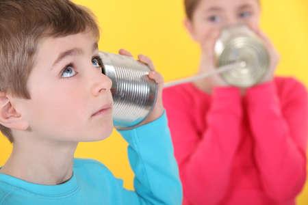 tin cans: Twee kinderen communiceren met blikje en string Stockfoto