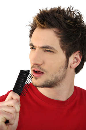 young man holding hairbrush as makeshift microphone photo
