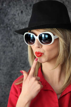 Pouting woman in sunglasses and hat photo