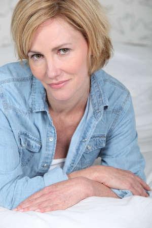 unpretentious: Closeup portrait of a blonde woman lying on a bed in a denim shirt