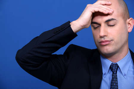 pounding head: Businessman stressed out at work