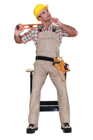 carpenter holding a level and thinking Stock Photo - 11912530