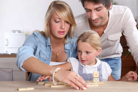 A cute little girl playing dominos with her parents. photo