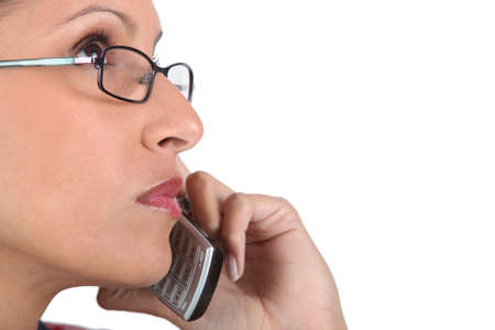 Woman wearing glasses using telephone photo