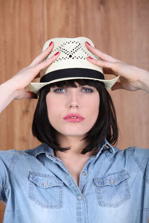 brunette with hands on strawhat photo