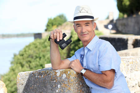60 64 years: Older male tourist with binoculars leaning on the citadel walls at Blaye in SW France